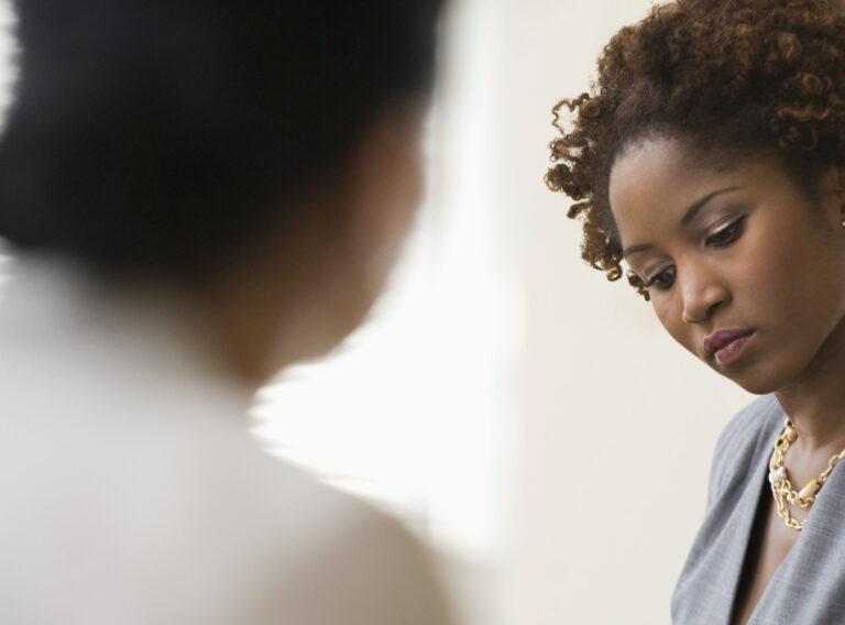 Black businesswoman writing during meeting
