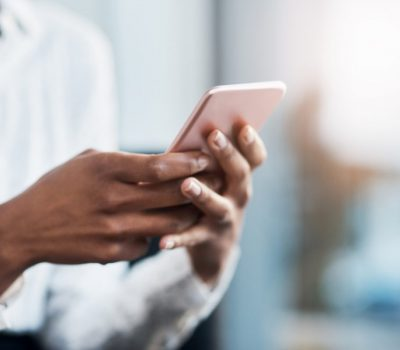 Cropped shot of a businesswoman using a mobile phone in a modern office